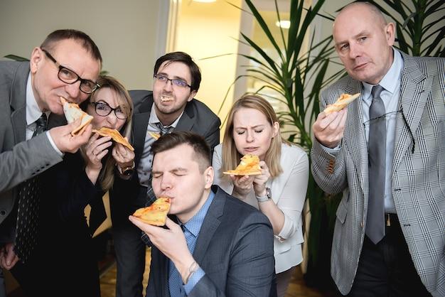 Glückliches geschäftsteam, das pizza im büro isst