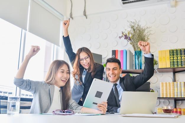 Glückliches geschäftsteam mit dem arm angehoben in büro nach dem treffen des glücklichen erfolgs
