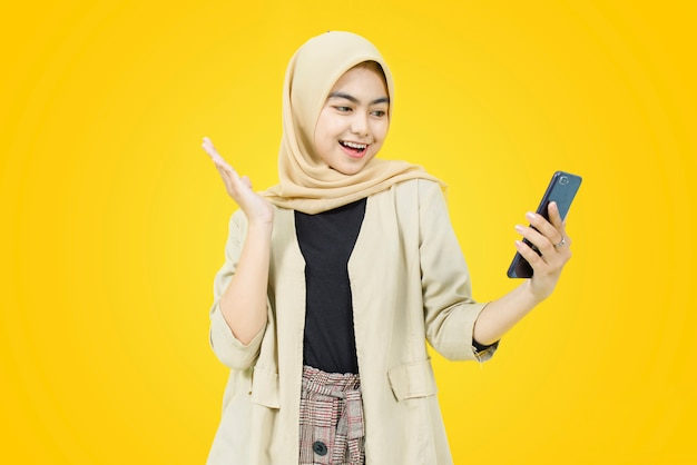 Glückliches gesicht der jungen asiatischen frau mit smartphone auf gelber wand