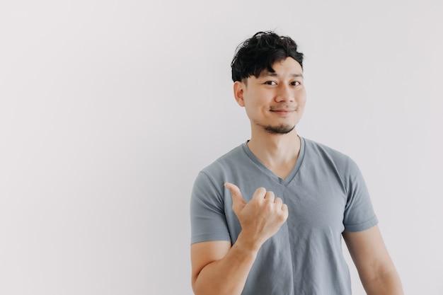 Glückliches gesicht des asiatischen mannes blick auf einen leeren raum isoliert auf weißer wand