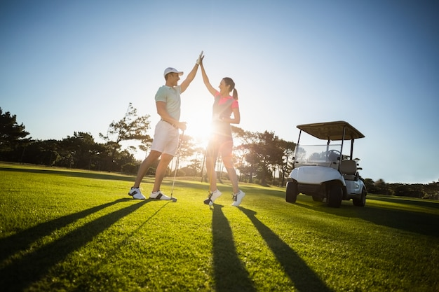 Glückliches golfspielerpaar, das hohe fünf gibt