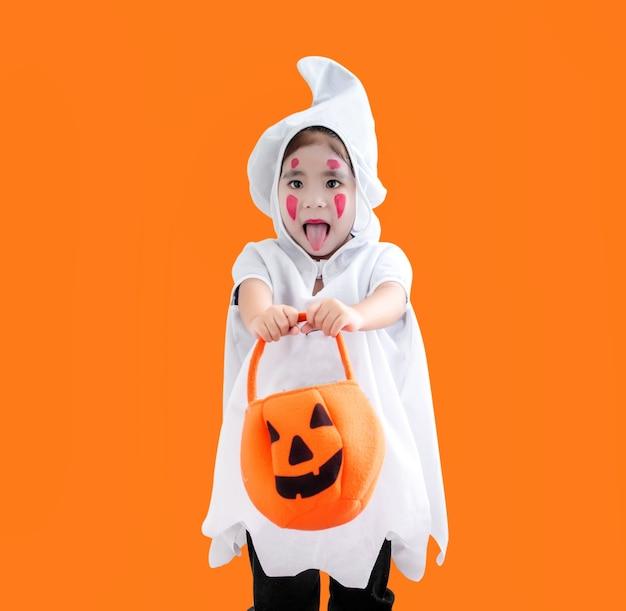Glückliches hallooween asiatisches kind im geisterkostüm auf orange mit beschneidungspfad