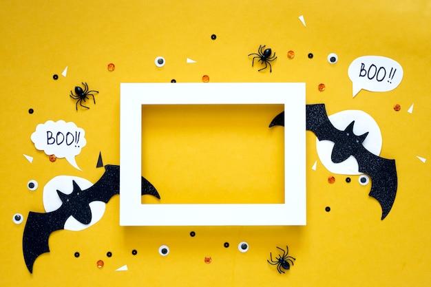 Glückliches halloween-feiertagskonzept. schwarze glitzerpapierfledermäuse auf hellgelbem hintergrund mit mond, schwarzer spinne, augen, konfetti. halloween-party-grußkarte. rechtschreibwort boo. rahmenmodell für text