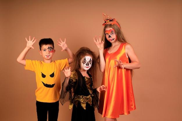 Glückliches halloween-porträt von kindern in den kostümen auf einer beigen wand