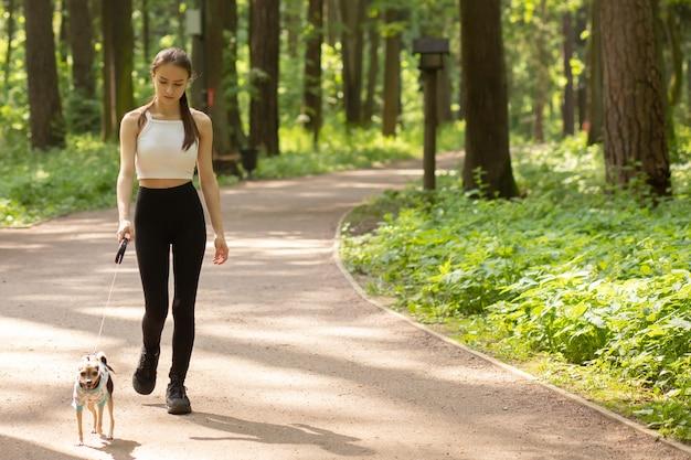 Glückliches haustier. ein junges mädchen geht mit einem kleinen hund im park spazieren