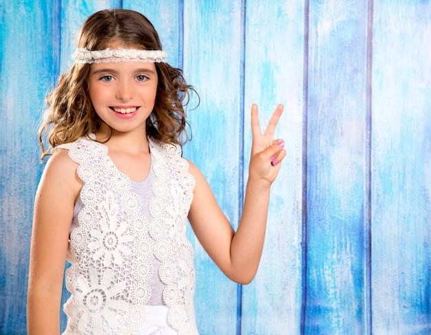 Glückliches hippiekindermädchen, das mit friedenshandzeichen lächelt