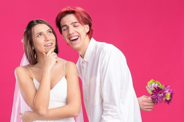 Glückliches hochzeitspaar bräutigam und braut, die einen glücklichen und fröhlichen bräutigam suchen, der blumen hinter seiner lächelnden braut im hochzeitskleid hält