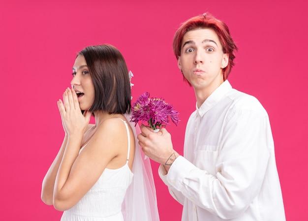 Glückliches hochzeitspaar bräutigam und braut glücklicher und fröhlicher bräutigam, der blumen für seine lächelnde braut im hochzeitskleid gibt, das über rosafarbener wand steht