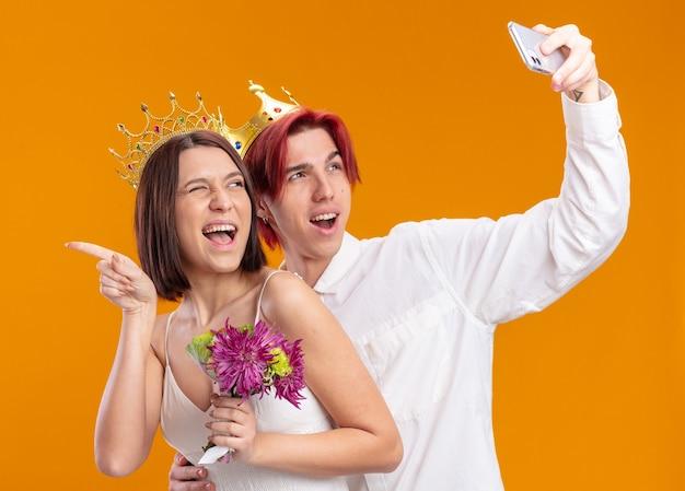 Glückliches hochzeitspaar bräutigam und braut mit blumenstrauß im hochzeitskleid mit goldenen kronen, die fröhlich lächeln und selfie mit smartphone machen