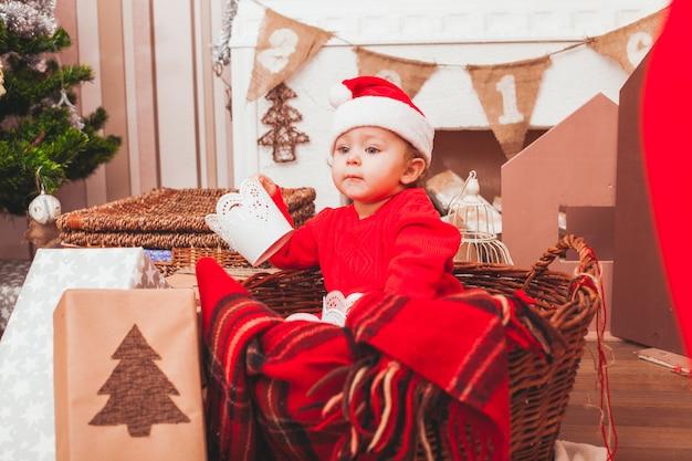 Glückliches hübsches baby im kostüm weihnachtsmann mit weihnachtsgeschenken