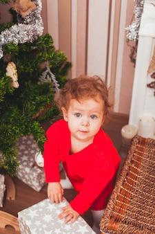 Glückliches hübsches baby im roten kleid mit weihnachtsgeschenken gekleidet