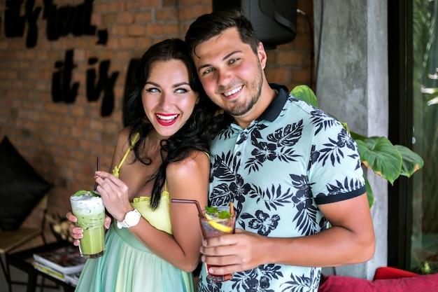 Glückliches hübsches junges paar, das ihren leckeren süßen cocktail an der tropischen bar genießt, farblich passende trendige kleidung, sommerferienstimmung. perfektes romantisches date.
