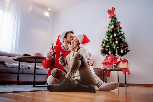 Glückliches hübsches kaukasisches paar mit weihnachtsmützen auf köpfen, die auf dem boden mit bierflasche in den händen sitzen und kuscheln. im hintergrund ist weihnachtsbaum mit geschenken darunter. wohnzimmer interieur.