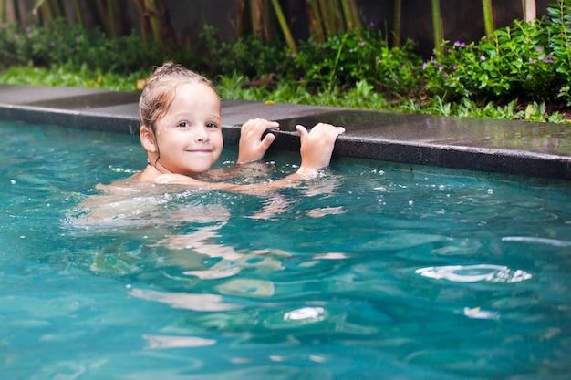 Glückliches hübsches kleines mädchen im schwimmbad im freien