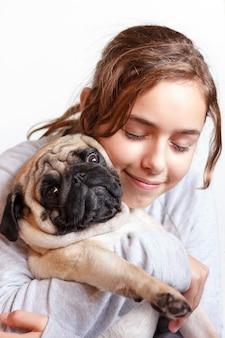 Glückliches hübsches lächelndes jugendlichmädchen, das pughund mit liebe umarmt