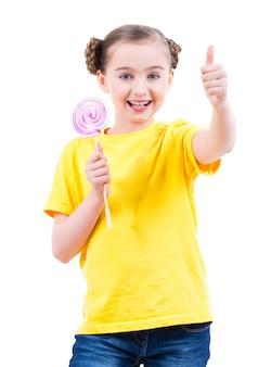 Glückliches hübsches mädchen im gelben t-shirt mit farbiger süßigkeit, die daumen hoch zeichen zeigt - lokalisiert auf weiß.