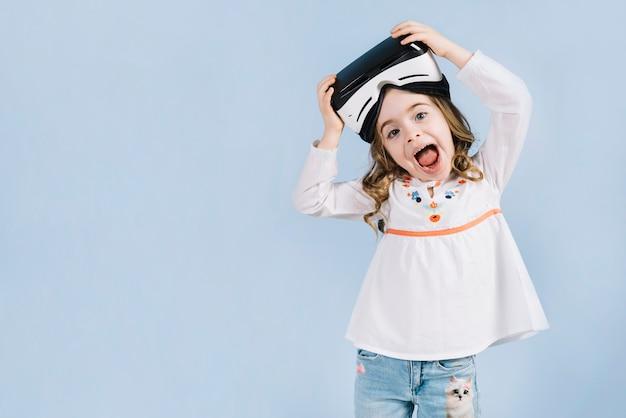 Glückliches hübsches mädchen mit virtuellem kopfhörer auf ihrem kopf gegen blauen hintergrund