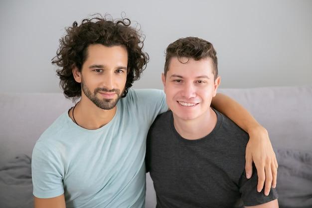 Glückliches hübsches schwules paar, das zu hause aufwirft, zusammen auf der couch sitzt und sich umarmt. vorderansicht. liebes- und beziehungskonzept