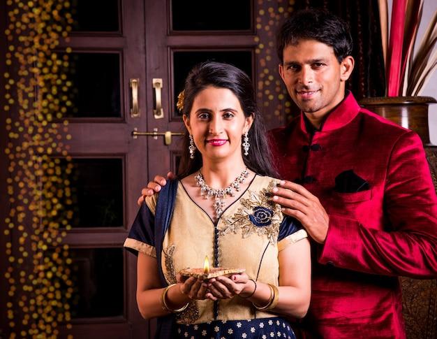 Glückliches indisches junges paar in namaskara oder gefaltete hände posieren auf dem diwali-festival und begrüßen gäste