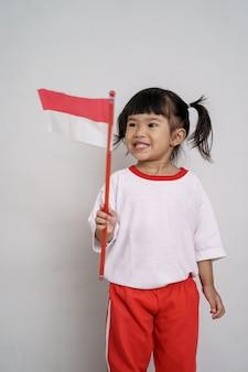 Glückliches indonesisches kind mit flagge