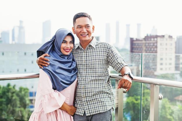 Glückliches indonesisches paar auf einem balkon in jakarta