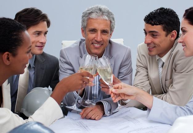 Glückliches ingenieurteam, das einen erfolg mit champagner feiert