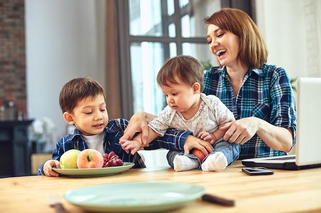 Glückliches internationales familienkonzept. vater, mutter, sohn und kleine tochter, die zu hause für eine kamera posieren, beschäftigen sich mit der elternschaft. ferien zu hause, elternschaft, konzeptkinder und eltern.