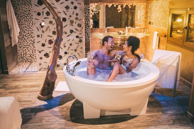 Glückliches interracial paar entspannte sich im whirlpool, genoss sich und trank wein