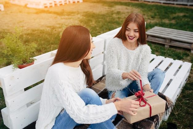 Glückliches jugendlich ein geschenk an ihre freundin zu geben