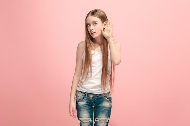Glückliches jugendlich mädchen, das auf trendigem rosa steht und hört. schönes weibliches halblanges porträt