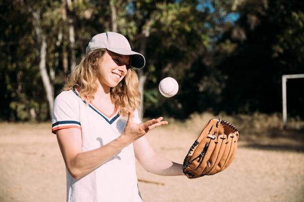 Glückliches jugendlich mädchen, das baseball spielt