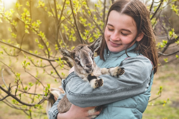 Glückliches jugendlich mädchen, das eine ziege in ihren armen hält