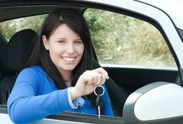 Glückliches jugendlich mädchen, das in ihrem auto hält schlüssel sitzt
