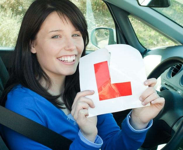Glückliches jugendlich mädchen, das in ihrem auto reißt ein l-zeichen sitzt