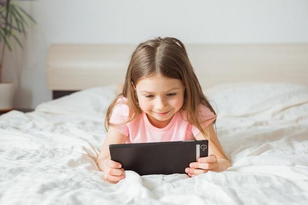 Glückliches jugendlich mädchen, das online-film-stream mit digitalem handy-tablet sieht und am morgen zu hause auf dem bett liegt
