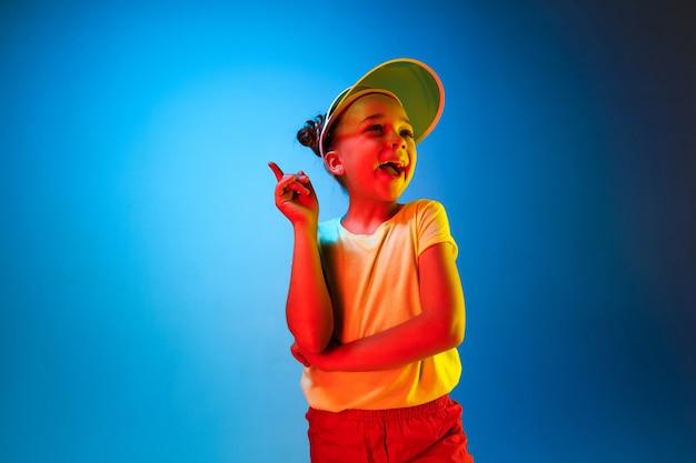 Glückliches jugendlich mädchen, das steht, lächelt und über trendigen blauen neonraum zeigt. schönes weibliches porträt. junge befriedigen mädchen