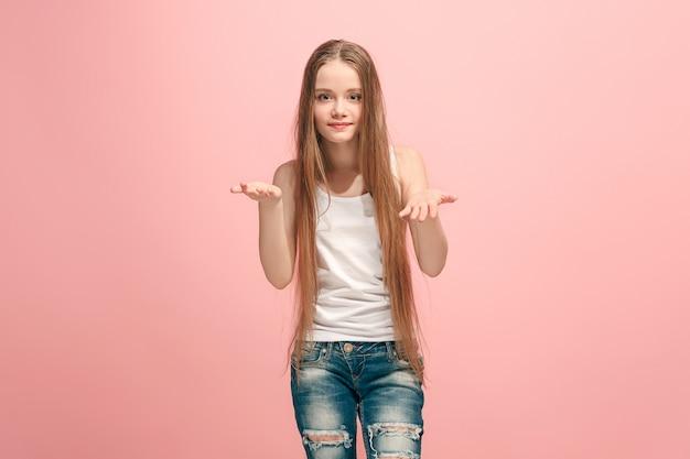 Glückliches jugendlich mädchen, das steht und etwas auf dem trendigen rosa studiohintergrund anbietet. schönes weibliches halblanges porträt. menschliche emotionen, gesichtsausdruckkonzept.