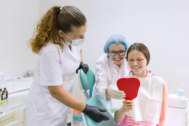 Glückliches jugendlich mädchen im zahnmedizinischen stuhl