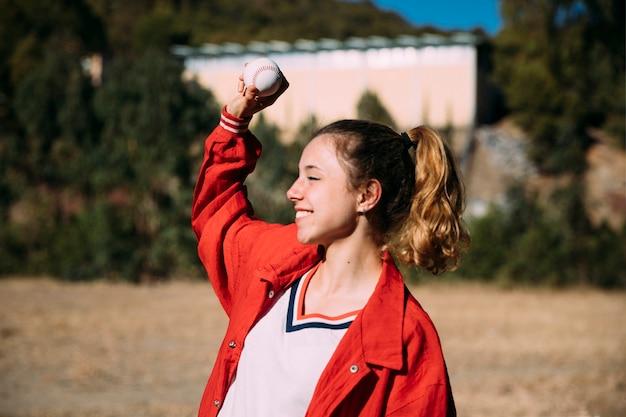 Glückliches jugendlich mädchen mit ball für baseball