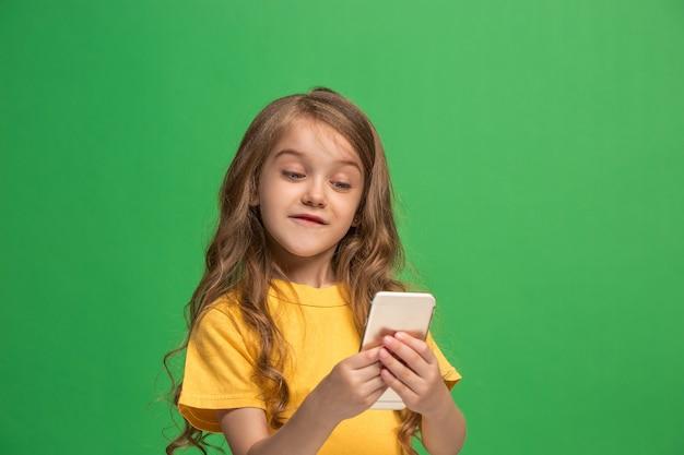 Glückliches jugendlich mädchen stehend, lächelnd mit handy über trendigem grünem studiohintergrund.