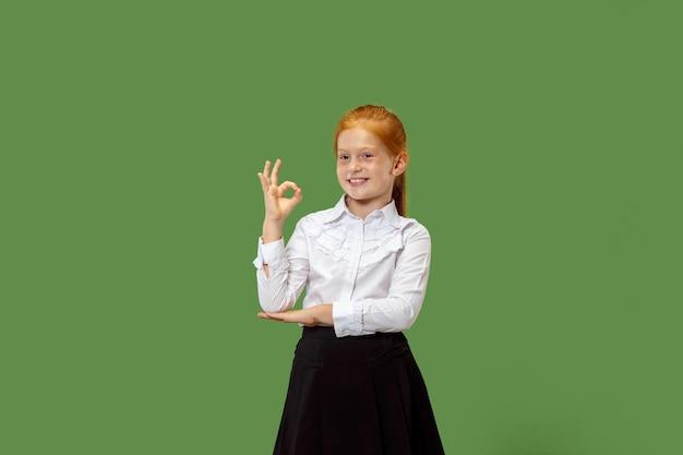 Glückliches jugendlich mädchen stehend, lächelnd und auf sich selbst lokalisiert auf trendigem grünem studiohintergrund. schönes weibliches halblanges porträt. menschliche emotionen, gesichtsausdruckkonzept.