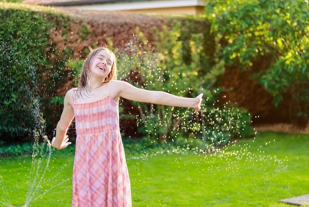Glückliches jugendliches mädchen, das glücklich im sommergarten unter wassertropfenspray von der wasserleitung lacht.