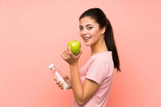 Glückliches jugendlichmädchen über lokalisierter rosa wand mit einer flasche wasser und einem apfel