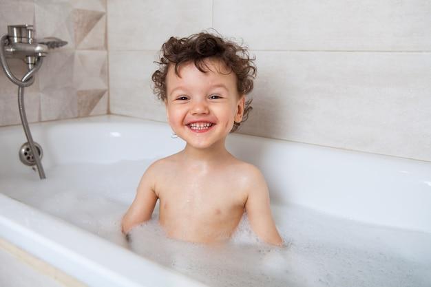 Glückliches jungenkind, das in einem bad mit schaum sitzt.