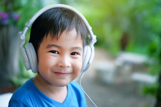 Glückliches jungenkind hören musik mit kopfhörer zu hause. lächeln gesicht porträt bild.
