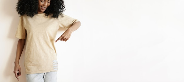 Glückliches junges afrikanisches modell mit afro-frisur, die an der weißen wand aufwirft, ihren zeigefinger auf stilvolles übergroßes zerrissenes t-shirt zeigt und lächelt. mode-, design- und bekleidungskonzept