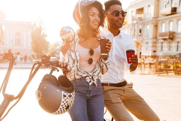 Glückliches junges afrikanisches paar, das kaffee trinkt, während es nahe dem modernen motorrad auf der straße steht und wegschaut