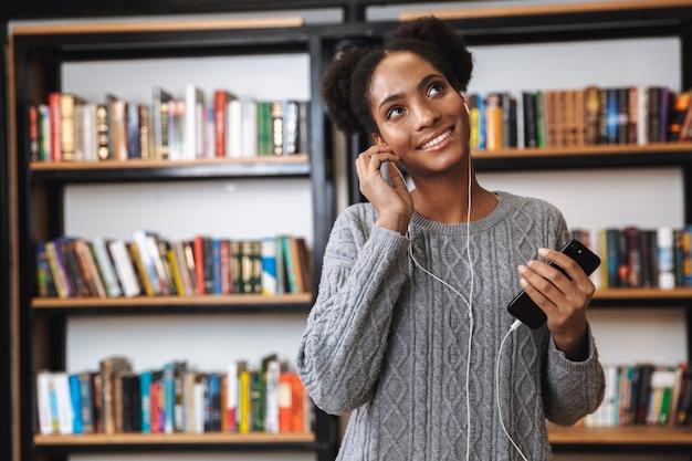 Glückliches junges afrikanisches studentenmädchen, das an der bibliothek studiert und musik mit kopfhörern hört