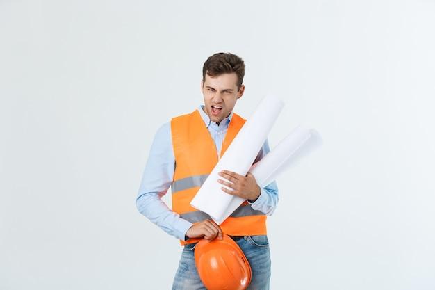 Glückliches junges architektenporträt mit helm und blaupausen im innenbereich.