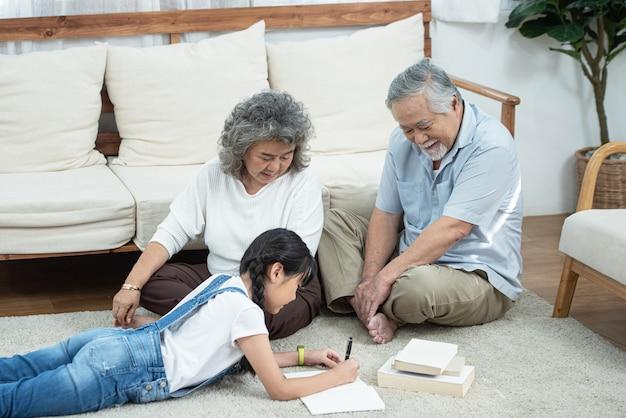 Glückliches junges asiatisches enkelin-lese- und schreibbuch mit großvater und großmutter, die neben auf boden im wohnzimmer zu hause suchen, häusliches ruhestandslebenskonzept.